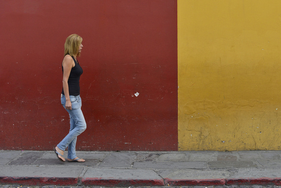 The colorful wall of Antigua, Guatemala as people walk by. Photography by Peter Stanley, 2012